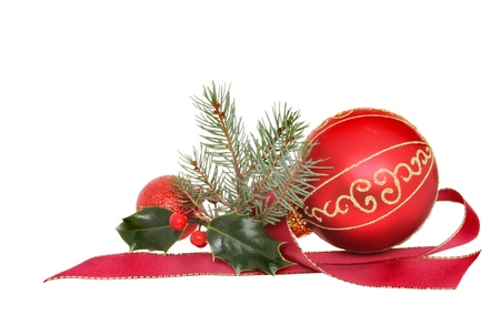 christmas motif: Christmas decoration, red and gold baubles with holly fir tree foliage and red ribbon isolated against white
