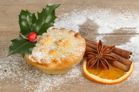 Holly decorated mince pie with dried orange, star anise and cinnamon on weathered wood dusted with icing sugar