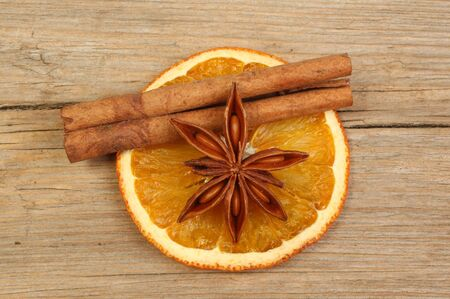 Slice of dried orange with star anise and cinnamon on old weathered wood photo