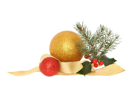 christmas motif: Christmas decoration of red and gold baubles, ribbon with holly and pine needles isolated against white