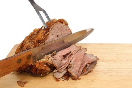 Carving roast beef, meat joint with a carving knife and fork on a wooden board