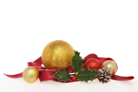 Christmas decoration of ribbon, baubles, holly and a pine cone against a white background photo