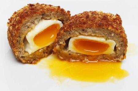 runny: Closeup of a runny yolk Scotch egg on a plate