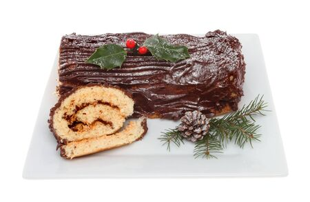 Chocolate yule log on a plate decorated with holly and seasonal foliage isolated against white photo