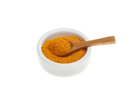 tumeric: Tumeric spice with a wooden spoon in a ramekin isolated against white Stock Photo