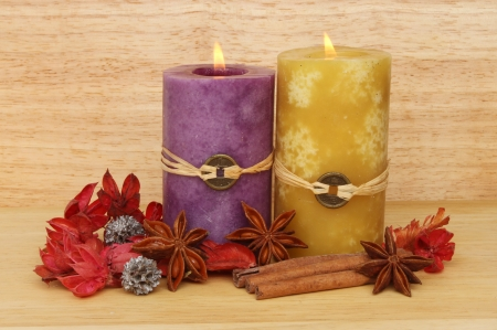 Two burning Feng Shui candle, potpourri, cinnamon and star anise against a wooden background Stock Photo - 18179051