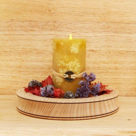 Yellow Feng Shui candle and potpourri in a wooden bowl on a wood background Stock Photo - 18179053