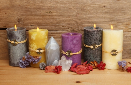 Burning Feng Shui candles, crystals and potpourri against a background of old rustic wood photo