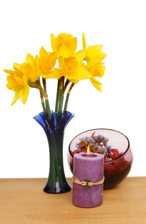 Daffodils, potpourri and burning Feng Shui candle on a table against a white background Stock Photo - 18179064