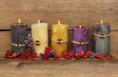 Five burning Feng Shui candles and potpourri on a background of old weathered wood photo