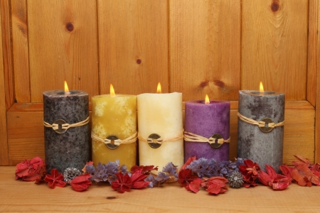 Five burning Feng Shui candles and potpourri against a wooden panel Stock Photo - 18179018