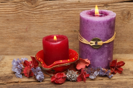 Red and purple candles with potpourri on a background of old weathered wood photo