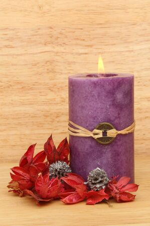 Purple burning Feng Shui candle and Potpourri against a bachground of warm colored wood Stock Photo - 18179049