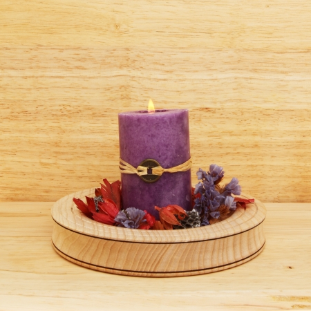 Burning purple Feng Shui candle with potpourri in a wooden bowl Stock Photo - 18179058