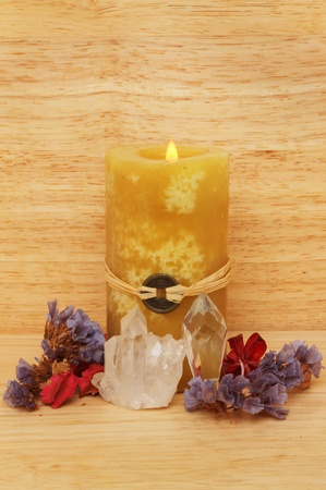 Burning yellow Fenf Shui candle, potpourri and crystals against a wooden background Stock Photo - 18179052