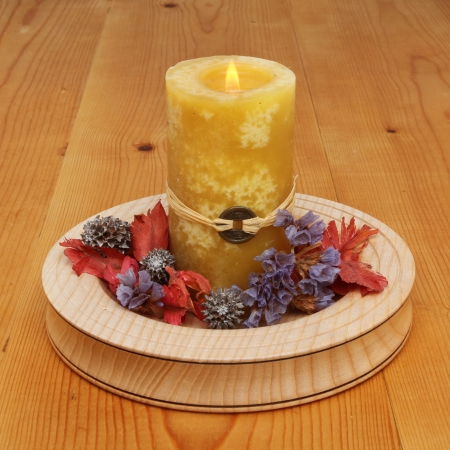 Burning yellow Feng Shui candle with potpourri in a wooden dish on a table Stock Photo - 18179040