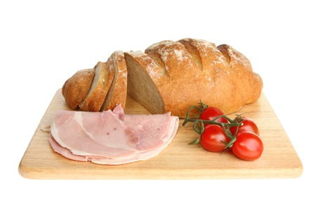 bloomer: Freshly baked bloomer loaf with ham and tomatoes on a wooden board isolated against white Stock Photo