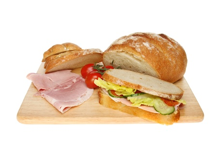 bloomer: Freshly baked bloomer loaf, sandwich, ham and tomatoes on a wooden board isolated against white