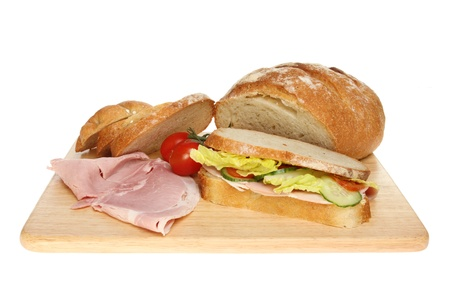 bloomer: Sandwich and freshly baked bloomer loaf with ham and tomatoes on a wooden board isolated against white