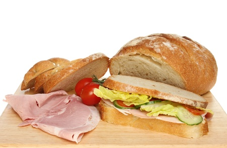bloomer: Closeup of a freshly baked bloomer loaf, sandwich with ham and tomatoes on a wooden board