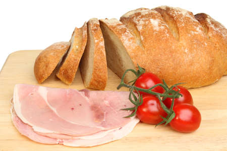 bloomer: Freshly baked bloomer bread loaf with ham and tomatoes on a wooden board