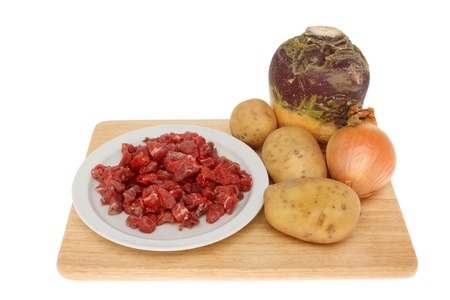 swede: Basic ingredients for the filling of a Cornish pasty, beef,swede,potato and onion on a wooden board isolated against white Stock Photo