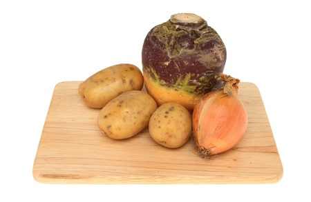 swede: Vegetable ingredients for a Cornish pasty,potato, swede and onion on a wooden board isolated against white