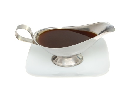 gravy: Meat gravy in a stainless steel gravy boat on a plate isolated against white
