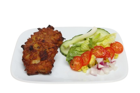 onion bhaji: Onion bhaji with a salad garnish on a plate isolated against white Stock Photo