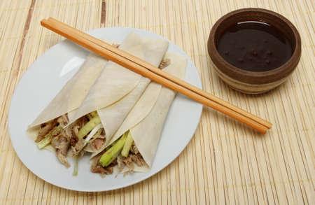 hoisin sauce: Chinese crispy duck pancakes, hoisin sauce and chopsticks on a bamboo matt
