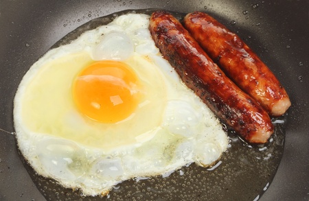 Closeup of sausages and an egg frying in a pan photo