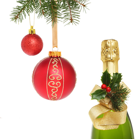 Christmas decorated champagne bottle and red baubles isolated against white photo