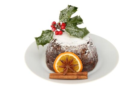 christmas pudding: Christmas pudding on a plate decorated with holly, orange, cinnamon and star anise isolated against white