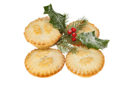 Mince pies decorated with holly and pine needles isolated against white
