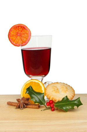 Mulled wine, mince pie and holly on a wooden board against a white background