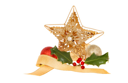 Christmas decoration of a gold star, ribbon, baubles and holly isolated against white photo