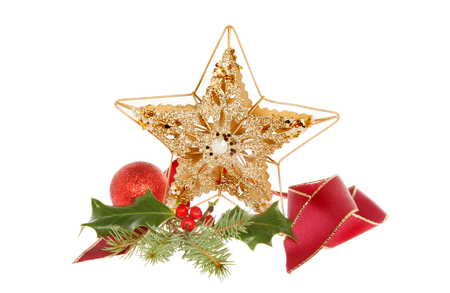 Christmas decoration, a gold glitter star with bauble, ribbon and seasonal foliage isolated against white photo