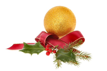Christmas decoration a gold glitter bauble with red ribbon and seasonal foliage isolated against white photo