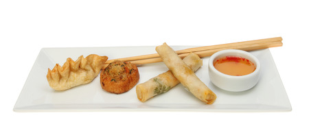 dim sum: Chinese Dim Sum snacks with a sweet chilli dip and chopsticks on a rectangular plate isolated against white Stock Photo