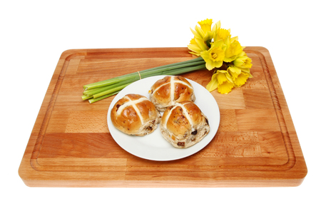 Plate of hot cross buns and a bunch on daffodils on a wooden board isolated against white