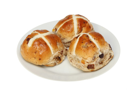 Three hot cross buns on a plate isolated against white