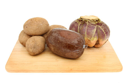 neeps: Haggis tatties and neeps on a wooden board isolated against white
