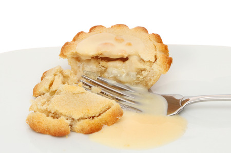 Closeup of an individual apple pie with custard and a fork on a plate photo