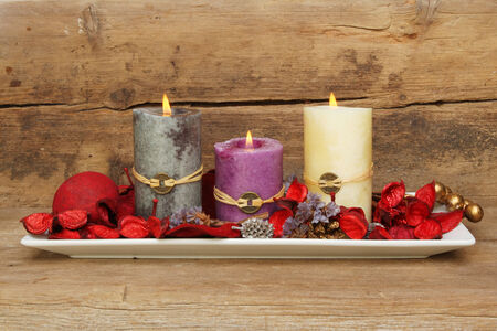 Three burning Feng Shui candles in a dish with potpourri against a background of old weathered wood photo