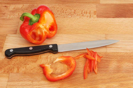 beechwood: Half of a red bell pepper, slices and a knife on a beechwood food preparation board Stock Photo
