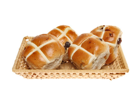 Hot cross buns in a wicker basket isolated against white