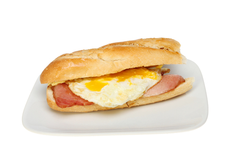 Bacon and fried egg in a baguette bread roll on a plate isolated against white photo