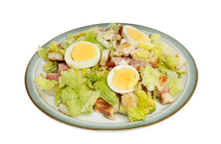 Caesar style salad with bacon and hard boiled egg on a plate isolated against white photo