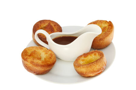 Yorkshire puddings with gravy in a jug on a plate isolated against white photo