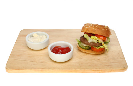 bap: Burger in a bap with ketchup and mayonnaise in ramekins on a wooden board isolated against white
